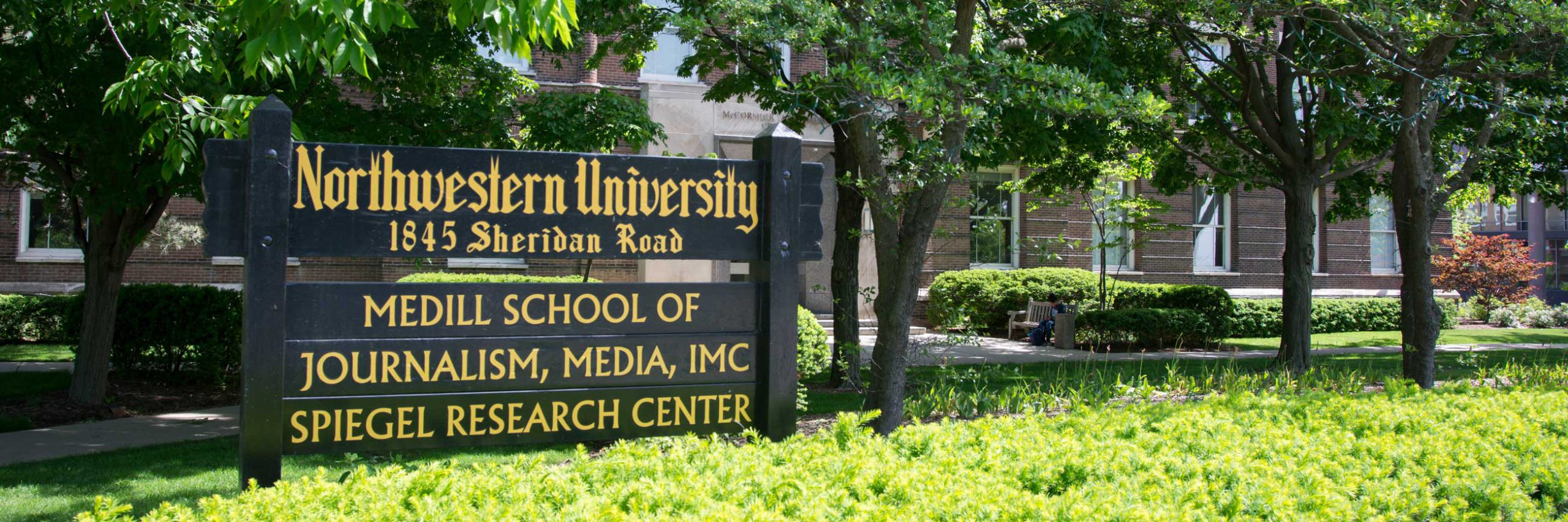 """A sign outside of a brick building. The sign reads """"Northwestern University, 1845 Sheridan Road, Medill School of Journalism, Media, IMC, Spiegel Research Center"""""""