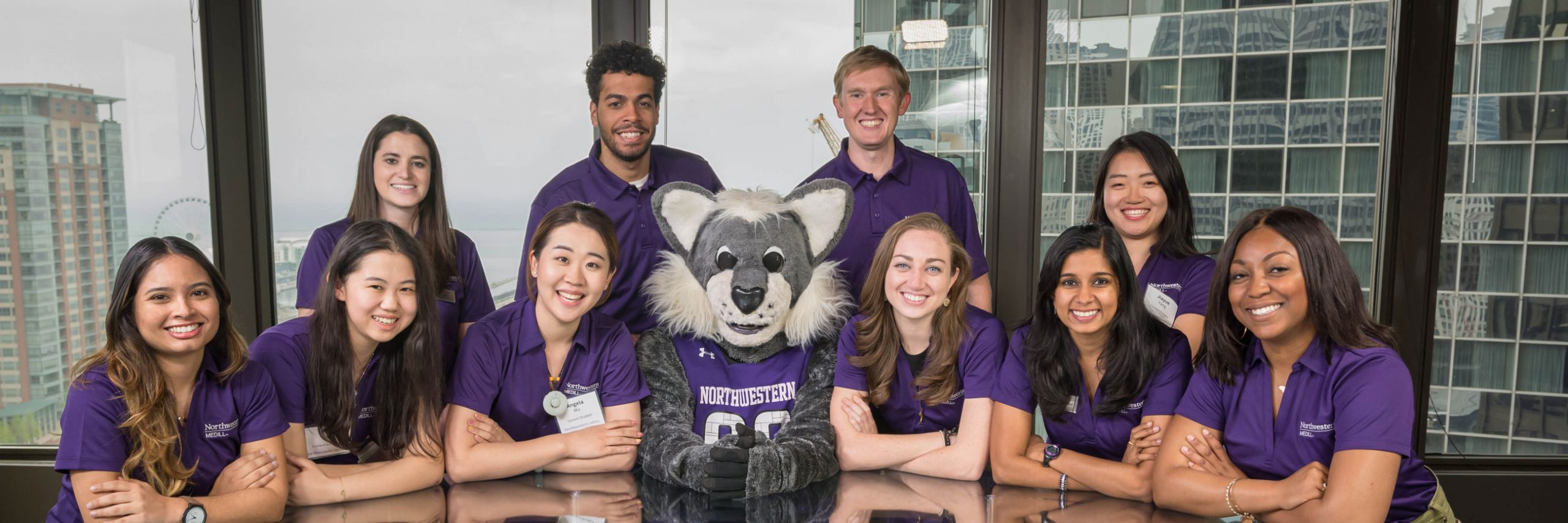 Students pose for a photo. They are wearing purple shirts with the Northwestern Medill logo on them and sitting with the Willie the Wildcat mascot.