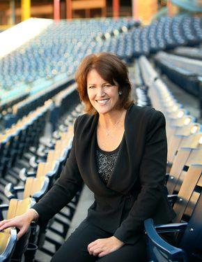 Professional photo of Christine Brennan sitting in stadium seats.