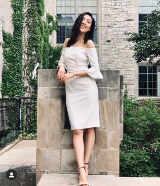Full body shot of Isabella Jiao standing in a campus courtyard.