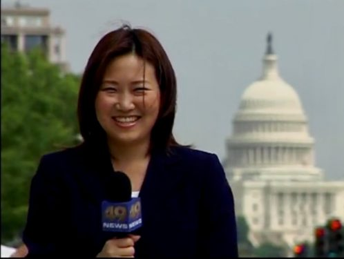 Ann Lee standing in front of a government building holding a news microphone.