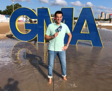 Photo of Jesse Kirsch reporting on the beach in front of a giant Good Morning America sign.