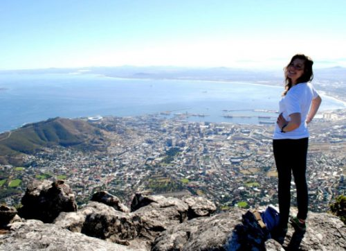 Lauren Manning standing at the top of a mountain looking over a city.