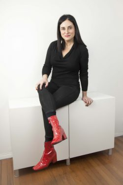 Full body shot of Michelle Madhok wearing bright red boots.