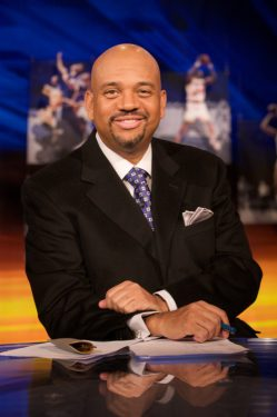 Photo of Mike Wilbon sitting at a desk.