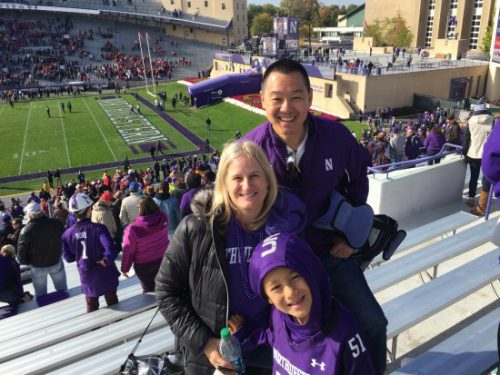 Victor Chi standing with his family at Ryan Field in Evanston, IL.