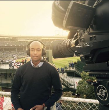 Photo of Will Jones on the job, reporting from a baseball stadium.