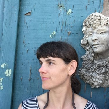 Selfie of Bridget Macdonald in front of a blue wall.