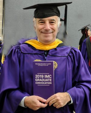 Roy Wollen in purple regalia holding a IMC 2019 Convocation pamphlet.