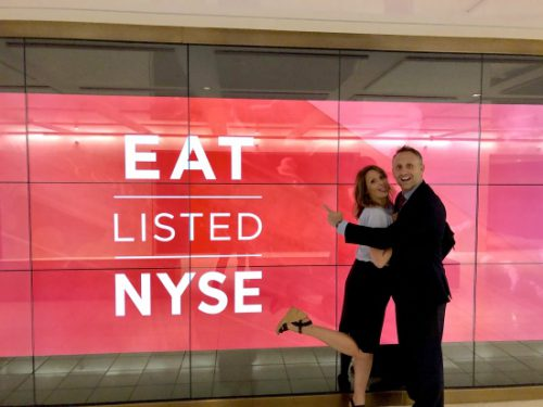 Wade Allen standing with a woman in front of a New York Stock Exchange sign.