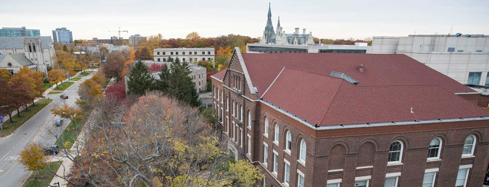 A brick building is shown from an aerial view. There is a street below with cars driving on it and a building with a tall steeple in the background.