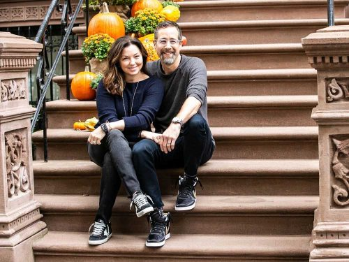 Kass and Mike Lazerow pose for a photo sitting on steps to a building.