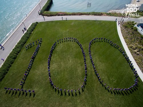 A drone image of students standing in the shape of a large 100. They are standing on an area of grass by a lake.